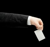 Caucasian male hand in a business suit isolated. Caucasian male hand in a business suit, holding the white empty business card, low-key lighting composition Royalty Free Stock Images
