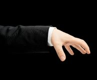 Caucasian male hand in a business suit isolated. Caucasian male hand in a business suit, palm holding something gesture sign, low-key lighting composition Stock Image
