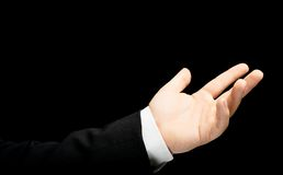 Caucasian male hand in a business suit isolated. Caucasian male hand in a business suit, showing the asking for help gesture sign, low-key lighting composition royalty free stock photos