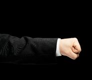 Caucasian male hand in a business suit isolated. Caucasian male hand in a business suit, showing the clenched in the fist gesture sign, low-key lighting Royalty Free Stock Photos
