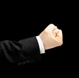 Caucasian male hand in a business suit isolated. Caucasian male hand in a business suit, showing the clenched in the fist gesture sign, low-key lighting Royalty Free Stock Images