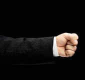 Caucasian male hand in a business suit isolated. Caucasian male hand in a business suit, showing the clenched in the fist gesture sign, low-key lighting Stock Photos