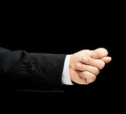 Caucasian male hand in a business suit isolated. Caucasian male hand in a business suit, showing the offensive fig gesture sign, low-key lighting composition Royalty Free Stock Photo