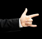 Caucasian male hand in a business suit isolated. Caucasian male hand in a business suit, showing the sign of horn gesture, low-key lighting composition, isolated stock photography