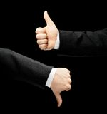 Caucasian male hand in a business suit isolated. Caucasian male hand in a business suit, showing thumbs up and down gesture signs, low-key lighting composition royalty free stock photography