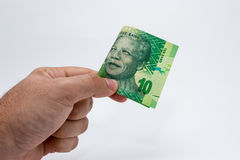 A Caucasian male hand holding a 10 Rand South African note. This image has a plain background.  Royalty Free Stock Image