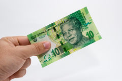 A Caucasian male hand holding a 10 Rand South African note. This image has a plain background.  Stock Image