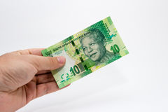A Caucasian male hand holding a 10 Rand South African note. This image has a plain background.  Royalty Free Stock Photography