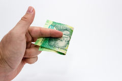 A Caucasian male hand holding a 10 Rand South African note. This image has a plain background.  Royalty Free Stock Photos