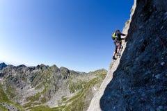 Caucasian male klättrare som klättrar en brant vägg Arkivfoto