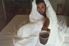 Caucasian male with lack of sleep because he has flu stting in bed and ask for water or medicine Royalty Free Stock Image