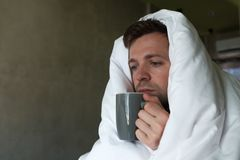 Caucasian male with lack of sleep because he has flu stting in bed and ask for water or medicine Royalty Free Stock Photo