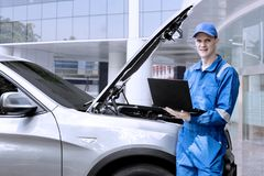 Caucasian mechanic repairing a car with laptop. Caucasian male mechanic looking at the camera while repairing a car by using a laptop Royalty Free Stock Photography