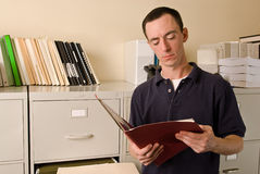 Caucasian male in file room reading papers inside a folder. A Caucasian male office worker in a file room reading papers inside a folder Royalty Free Stock Images