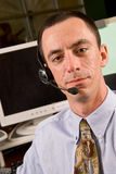 Caucasian Male Receptionist with Headset. A Caucasian male receptionist wearing a headset and looking toward the camera Royalty Free Stock Image
