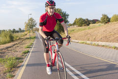 Caucasian Male Road Cyclist Having His Training Outdoors. Portrait of Professional Caucasian Male Road Cyclist Having His Training Outdoors. Going Uphill Stock Images