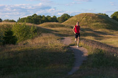 Caucasian, male runner in a summer landscape Stock Photos