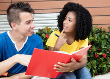 Caucasian male student learning with girlfriend. In the city in the summer Stock Image