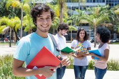 Caucasian male student with other international students. Outdoors on campus in summer Stock Image