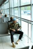 Caucasian male student sitting in waiting room at airport and listening to music. Caucasian male student sitting in waiting room at airport and listening to Royalty Free Stock Images