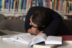 Caucasian Male Student Sleeping In Library. Sleeping Caucasian Student Sitting And Leaning On Pile Of Books In College - Shallow Depth Of Field Royalty Free Stock Images