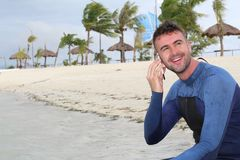 Caucasian male surfer calling from a vacation.  Royalty Free Stock Image