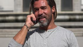 Caucasian Male Talking On Phone. A handsome Spanish adult male Stock Photo