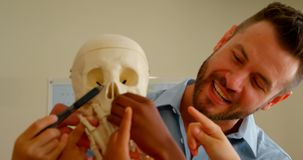 Caucasian male teacher fixing human skeleton model in classroom at school 4k. Front view of adult Caucasian male teacher fixing human skeleton model in classroom stock footage