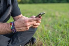 Caucasian male texting on cell, sitting on grass outside with rainbow bracelets stock photo