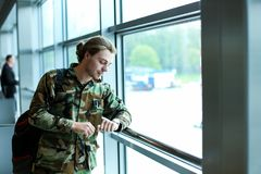 Caucasian male tourist looking at watch at airport waiting room, wearing camouflage jacket and backpack. Caucasian young male tourist looking at watch at Royalty Free Stock Photos