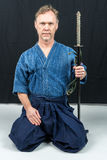 Caucasian male training Japanese sport, iaido. Sitting on floor holding a Japanese sword looking at camera. Stock Photos