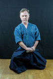 Caucasian male training Japanese sport, iaido. Sitting on floor about to draw a sword. Royalty Free Stock Image
