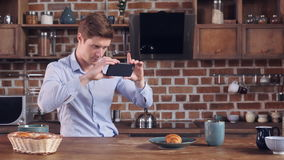 Caucasian male use smartphone photographed food. Handsome caucasian businessman taking photo his breakfast. Smiling man using smart phone using application stock footage