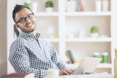 Caucasian male using laptop. Portrait of attractive european male in casual shirt and glasses using laptop computer at workplace Royalty Free Stock Images