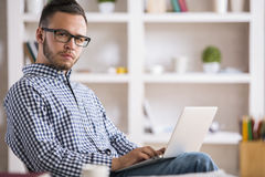 Caucasian male using laptop. Portrait of young caucasian male in casual shirt and glasses using laptop computer at workplace Stock Photos