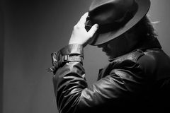 Caucasian male in vintage trench coat and fedora. Black and white with hand on hat. Caucasian male in vintage trench coat and fedora. Black and white Stock Photography