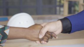 Caucasian man and African American woman shaking hands in front of the table. Designer and customer signed contract.