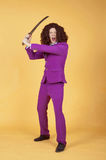 Caucasian man with afro wearing Purple Suit carrying sword Royalty Free Stock Photography