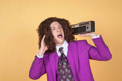 Caucasian man with afro wearing Purple Suit listening to music Royalty Free Stock Image