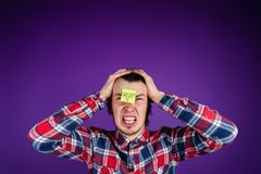 Caucasian man is angry with credit, grabs his head and cries, a close-up portrait. The man is shocked by the interest on. The loan. Credit card sticker - purple Royalty Free Stock Photos