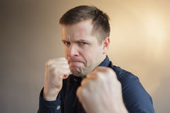 Caucasian man with angry mood. Young man protects himself by clenching his fists stock image