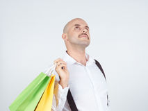 Caucasian man bald,  with colorful shopping paper bags Royalty Free Stock Photos