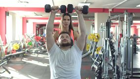 A caucasian man with a beard performs an exercise in the gym bench dumbbells sitting with the help of a beautiful girl