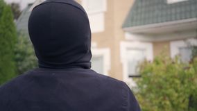 Caucasian man in black clothes and balaclava before breaking into house. The guy approaching big rich house. Concept of. Thief in black clothes and balaclava stock video footage