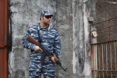 Caucasian man with black sunglasses in urban warfare holding gri Stock Photos
