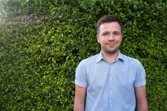 Caucasian man in blue shirt standing near green grass wall. He is smiling and feeling confident. Positive body language Royalty Free Stock Photos
