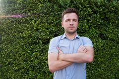 Caucasian man in blue shirt standing near green grass wall. He is smiling and feeling confident. Positive body language Royalty Free Stock Image
