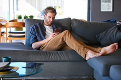 Caucasian man busy texting while sitting in a modern home Royalty Free Stock Photo