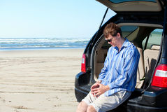 Caucasian man in car at beach, unhappy, worried expression Stock Photos