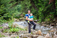 Caucasian man carrying his son in sling while hiking Stock Images